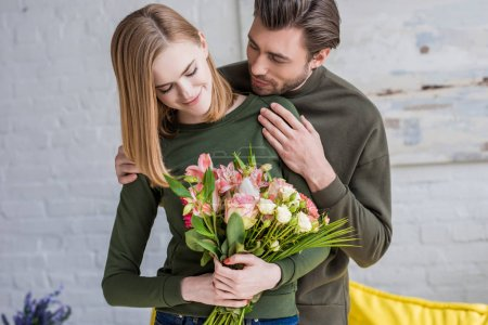 Photo for Smiling man embracing young girlfriend with flowers - Royalty Free Image