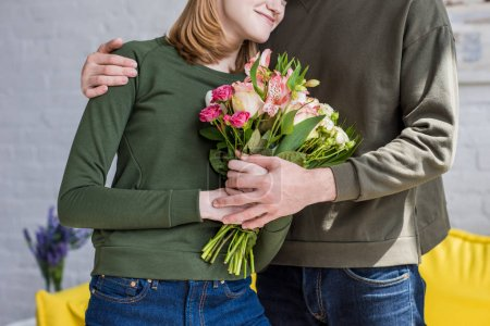 cropped image of man embracing smiling girlfriend with flowers