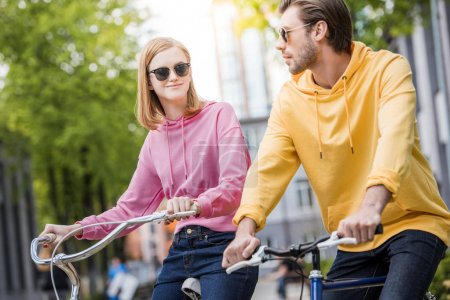 stylish young couple in sunglasses riding on bicycles