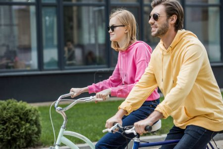 side view of stylish couple in sunglasses riding on bicycles
