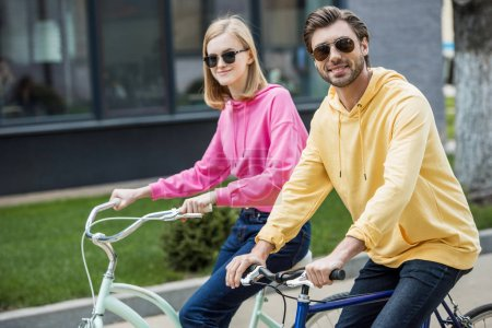 stylish couple in sunglasses riding on bicycles
