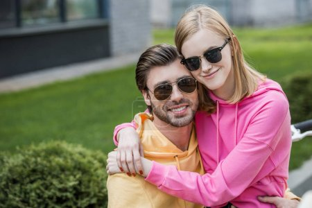 smiling young woman in sunglasses sitting on boyfriend knees and embracing him