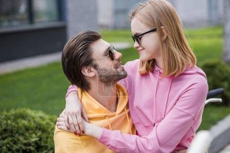 Photo pour Femme élégante en lunettes de soleil embrassant copain et assis sur ses genoux - image libre de droit