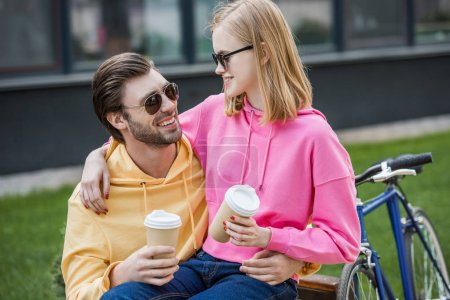 smiling stylish couple in sunglasses sitting on bench with papers cups of coffee