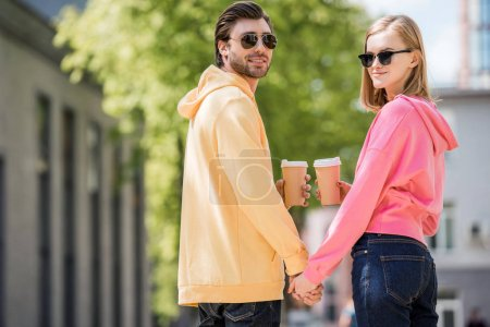 stylish couple in sunglasses with coffee cups holding hands of each other
