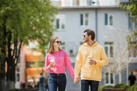 Photo for Stylish young couple in sunglasses with coffee cups holding hands and walking on street - Royalty Free Image