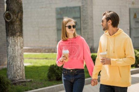Foto de Pareja joven con estilo en gafas de sol con tazas de café tomados de la mano y caminando en la calle - Imagen libre de derechos