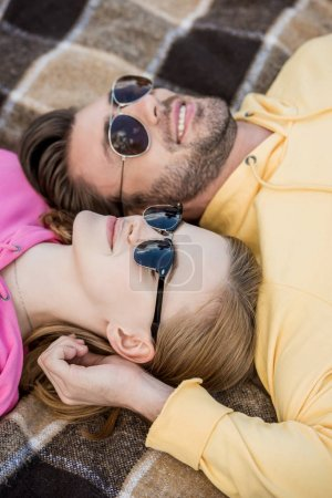 smiling couple in sunglasses laying on plaid