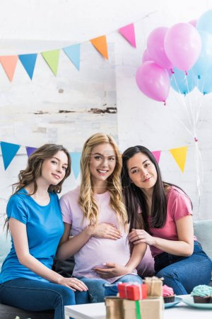 smiling multicultural friends and pregnant woman looking at camera during baby-party