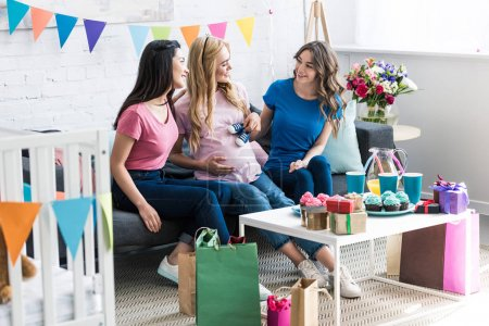 multicultural friends and pregnant woman having fun at baby-party