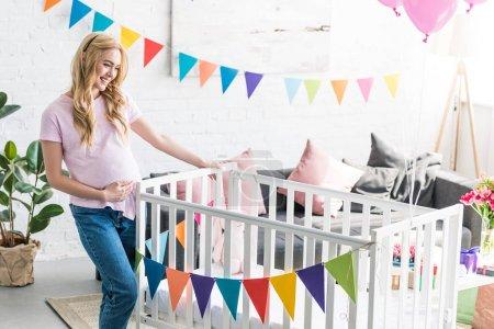 beautiful pregnant woman looking at new crib at baby-party