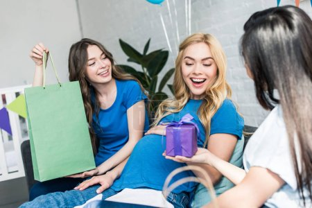 friends gifting presents to pregnant woman at baby-party