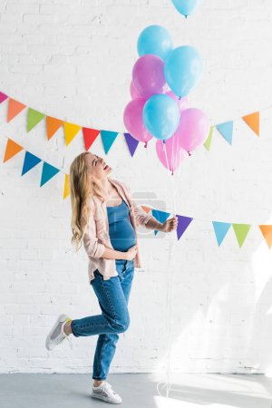 side view of happy beautiful pregnant woman holding bundle of balloons at baby-party