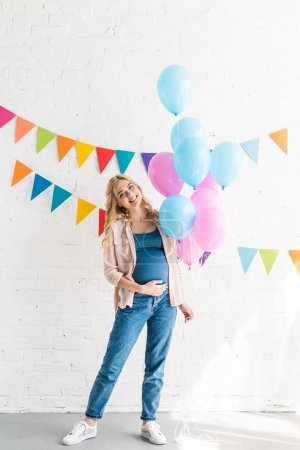 smiling beautiful pregnant woman holding bundle of balloons at baby shower party