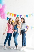 smiling multiethnic friends and pregnant woman looking at camera at baby-party