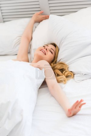 happy young woman waking up on white bed in morning