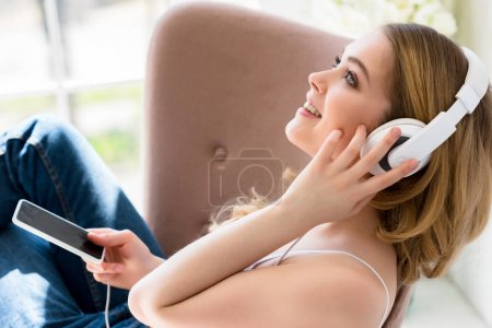smiling young woman listening music with headphones and smartphone on bed
