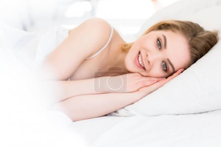 Photo for Beautiful smiling girl lying on white bed in morning - Royalty Free Image