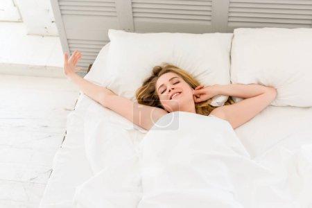 Photo pour Attrayant fille heureuse se réveiller sur le lit le matin - image libre de droit