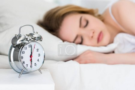 selective focus of girl sleeping on bed with alarm clock