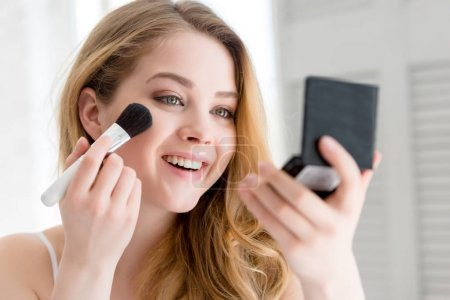 attractive smiling girl applying compact powder with brush and looking at mirror