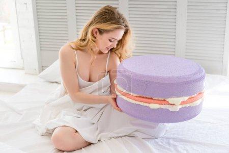 Photo pour Jolie jeune fille avec gros macaron mauve sur lit - image libre de droit
