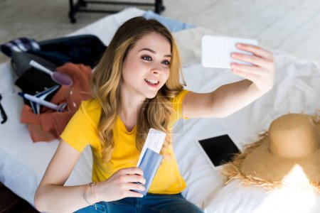happy young woman with passport and air ticket taking selfie on smartphone