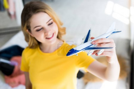 beautiful smiling young woman with airplane model