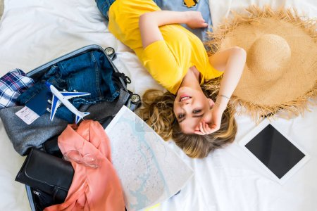 beautiful happy girl lying on bed with travel bag, airplane model, map and digital tablet