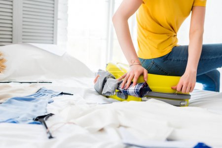 cropped view of young woman packing clothes into travel bag on bed