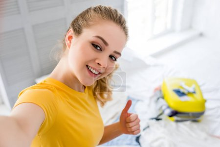 smiling girl taking selfie and showing thumb up while packing travel bag