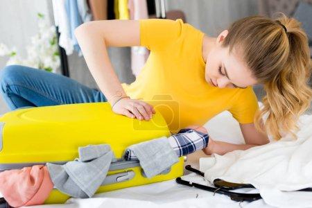 Photo pour Belle fille d'emballage des vêtements dans le sac de voyage sur lit - image libre de droit