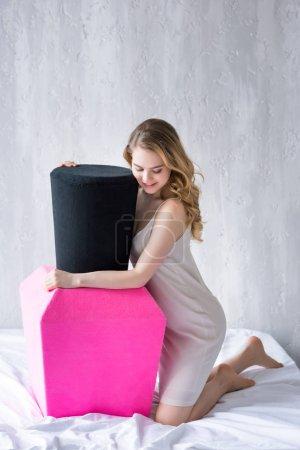 beautiful girl posing with big pink nail polish on bed