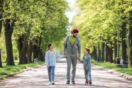 Photo pour Souriant père tenant la main du fils et de la fille et marchant dans le parc - image libre de droit