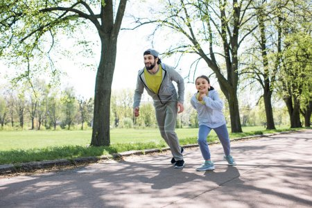 happy father and daughter running on path in park