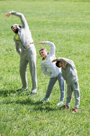 happy sportive family doing physical exercise on grass