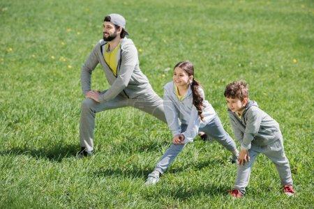 Photo pour Enfants et père faisant physique exercice sur Prairie dans le parc - image libre de droit