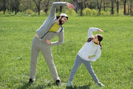 smiling daughter and father doing physical exercise on meadow in park