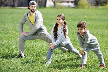 Photo pour Père et fille et faire des exercices physiques sur une prairie herbeuse dans le parc - image libre de droit