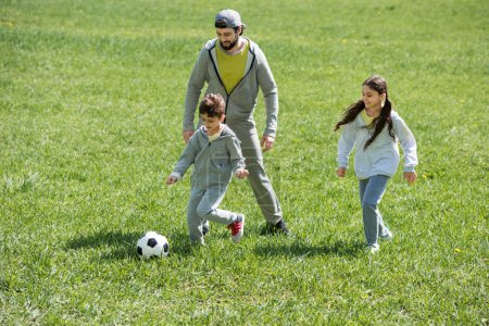 Photo for Father playing football with children on grass in park - Royalty Free Image