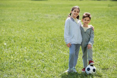 happy brother and sister with ball standing on grassy meadow