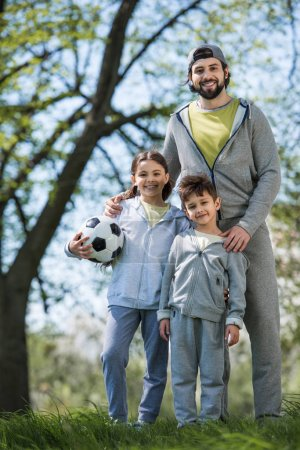 Photo for Happy family with soccer ball standing in park - Royalty Free Image