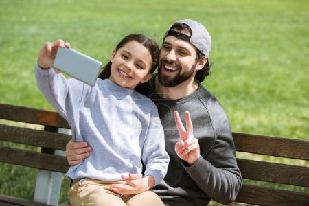 daughter taking selfie with father doing peace gesture in park