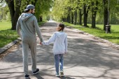 rear view of father and daughter holding hands and walking on path in park