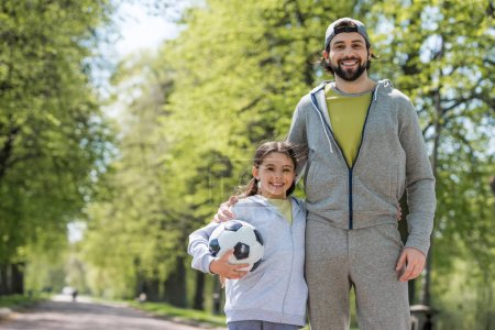 smiling father and daughter with ball in park