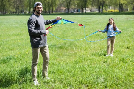 father and daughter with kite on grassy meadow in park