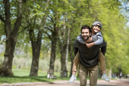 happy father doing piggyback ride to daughter in park