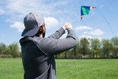 rear view of man flying kite on grassy meadow in park