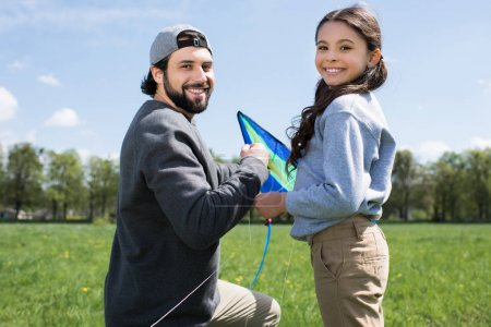 happy daughter and father with kite on meadow in park