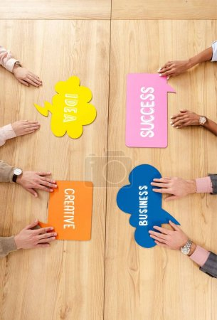overhead view of multiracial business people at wooden table with colorful chat bubbles with success, idea, creative, business signs